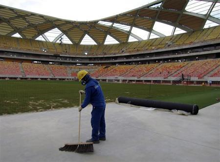 A workman sweeps next to the pitch inside the Arena Amazonia stadium as work continues in preparation for the 2014 FIFA World Cup soccer championship in Manaus