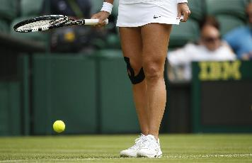 Li Na's right knee has been taped like this for about as long as she's been on the tennis radar. (AP Photo/Pavel Golovkin)