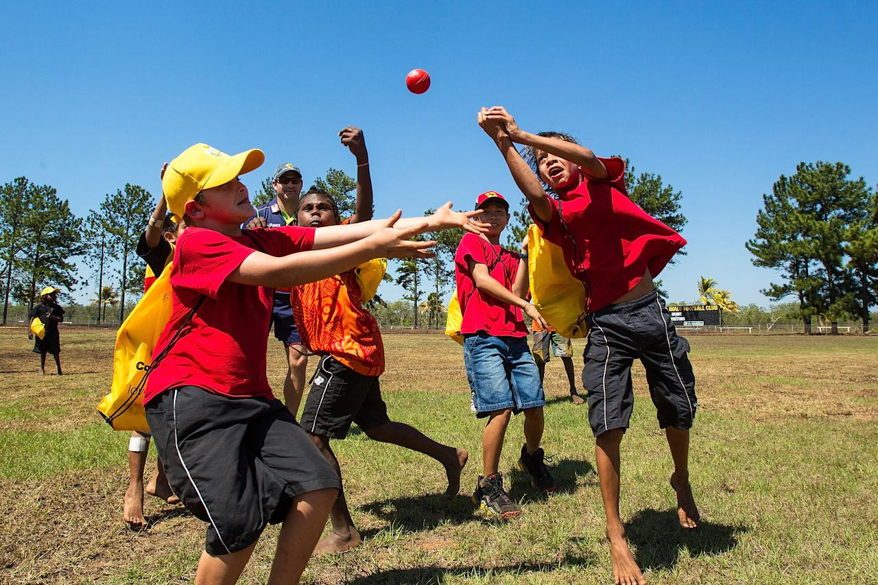 DARWIN, AUSTRALIA - AUGUST 10:  Ryan Harris of the Australian cricket team plays cricket with children during a visit to Pirlangimpi of the Tiwi Islands on August 10, 2012 on the Tiwi Islands, Australia.  (Photo by Mark Nolan/Getty Images)