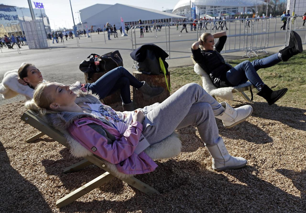 Women lay in the sun outside the Swiss House at the 2014 Winter Olympics, Wednesday, Feb. 12, 2014, in Sochi, Russia. Temperatures are predicted near 60 degrees Fahrenheit in Sochi on Wednesday. (AP Photo/Morry Gash)