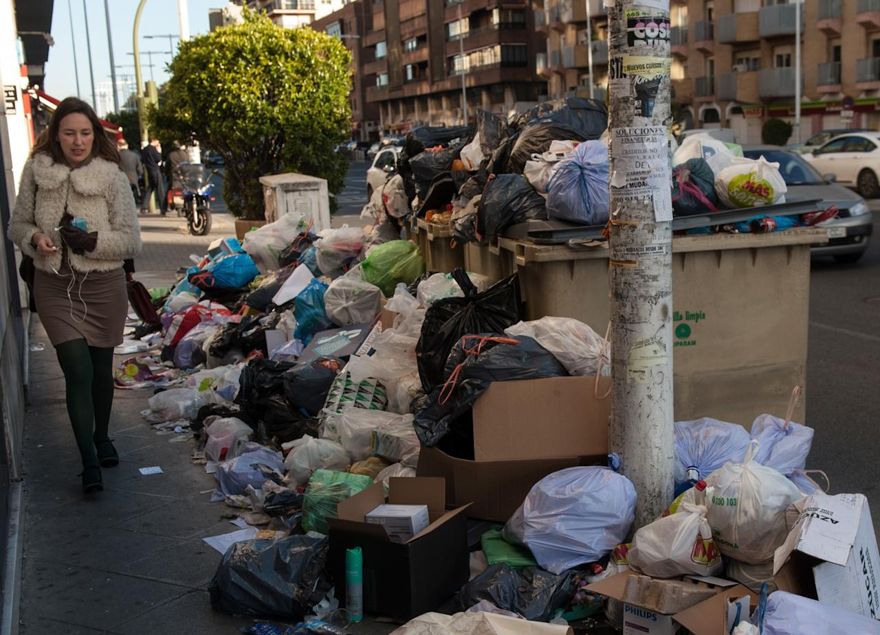 SEVILLE, SPAIN - FEBRUARY 06:  A pedestrian passes a pile of garbage during the 10th day of the Seville waste disposal strike on February 6, 2013 in Seville, Spain. Workers are striking over demands they take a 5% pay cut and extent their working week to 37.5 hours.  (Photo by Denis Doyle/Getty Images)