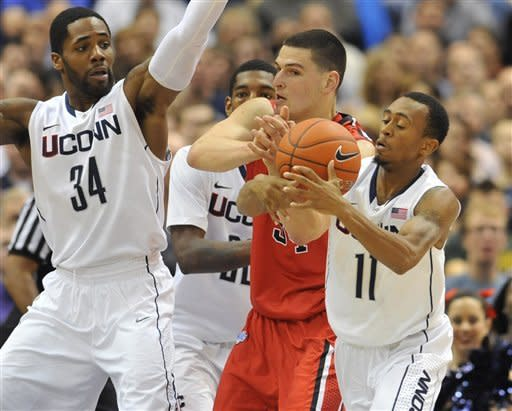 Connecticut's Ryan Boatright (11) steals the ball from Fairfield's Ryan Olander, center, as Connecticut's Alex Oriakhi (34) defends in the first half of an NCAA college basketball game in Hartford, Conn., Thursday, Dec. 22, 2011.  (AP Photo/Jessica Hill)