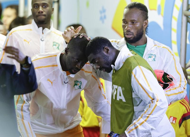 Ivory Coast's Kolo Toure and Yaya Toure, left,  greet each other as Didier Drogba watches before the group C World Cup soccer match between Ivory Coast and Japan at the Arena Pernambuco in Recife, Brazil, Saturday, June 14, 2014