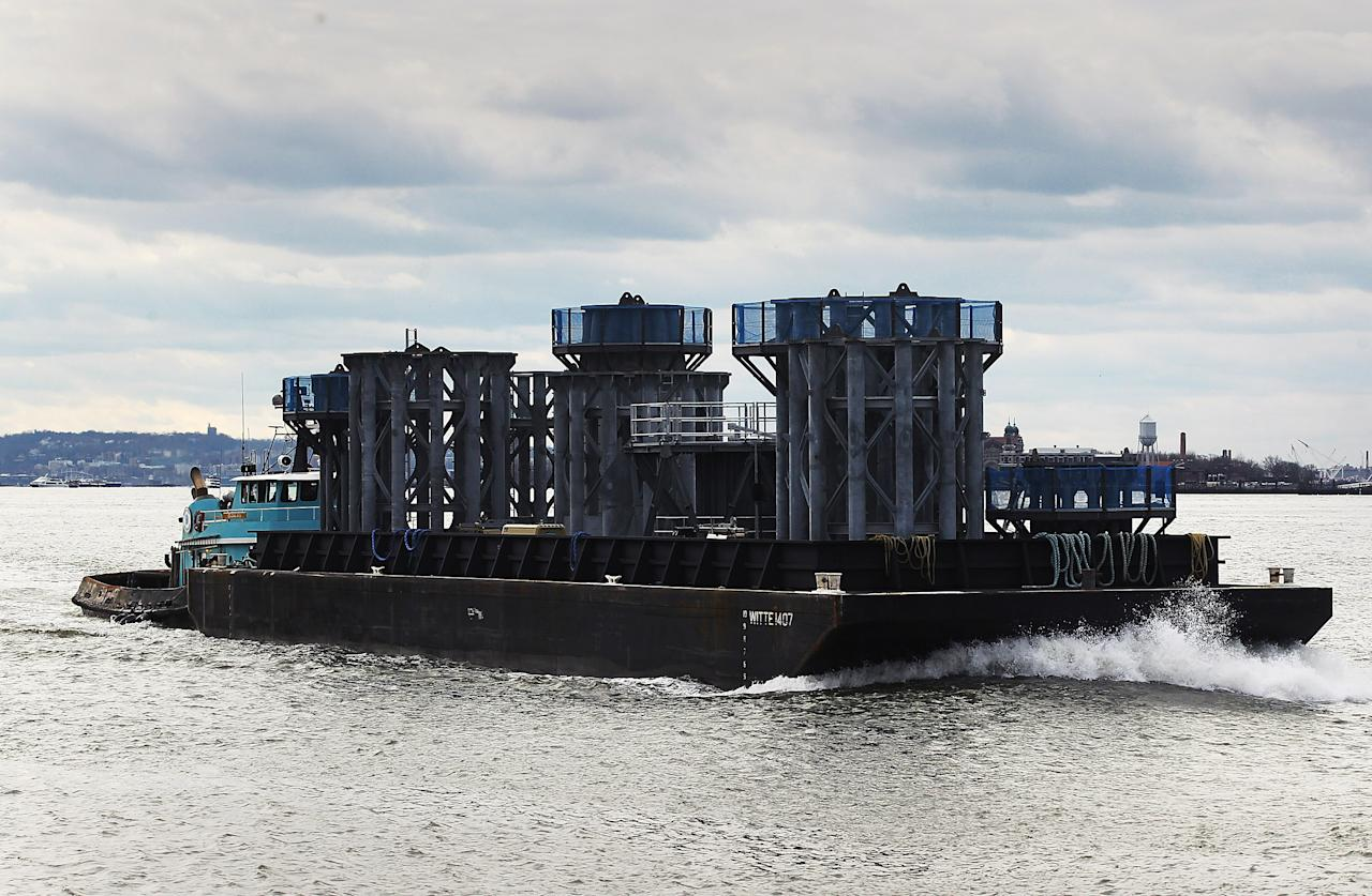Sections of the crowning spire for One World Trade Center arrive on a barge on the Hudson River on December 11, 2012 in New York City. The barge is carrying nine pieces of steel that will eventually  top off One World Trade Center out at a symbolic 1,776 feet, becoming the tallest building in the Western Hemisphere.  (Photo by Mario Tama/Getty Images)