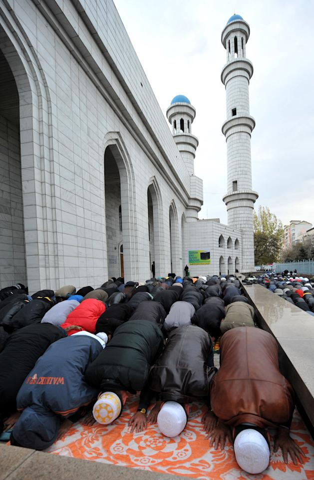 Kazakh Muslims pray outside a mosque in Almaty on November 16, 2010, during the Eid al-Adha (Kurban Bairam) holiday. Eid al-Adha, or the Feast of the Sacrifice, follows the annual pilgrimage to Mecca. It commemorates the willingness of biblical patriarch Abraham to sacrifice his son Ishmael and during the period Muslims distribute food to the poor.  AFP PHOTO / VYACHESLAV OSELEDKO