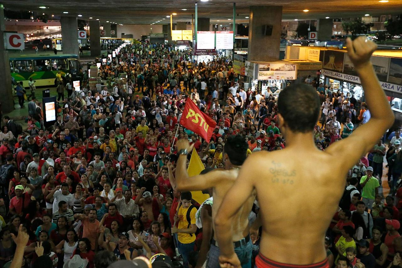 Demonstrators shout slogans against FIFA during a protest against FIFA World Cup, at the bus station in Brasilia, Brazil, Tuesday, May 27, 2014. Brazilians are protesting against the huge amounts of money spent by the government on the upcoming World Cup that starts in June. (AP Photo/Eraldo Peres)