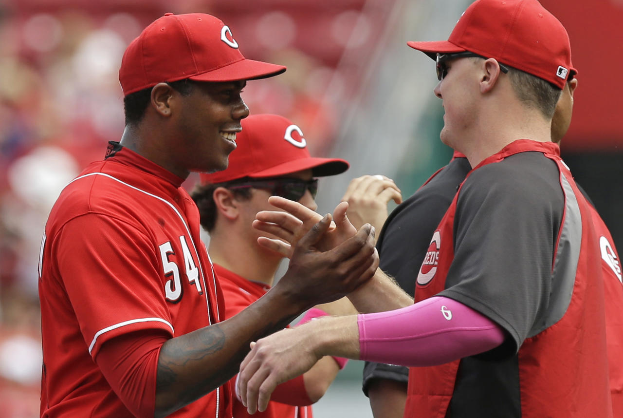 Cincinnati Reds relief pitcher Aroldis Chapman, left, is congratulated by Jay Bruce after Chapman earned his first save of the year in the Reds 4-1 win over the Colorado Rockies in a baseball game, Sunday, May 11, 2014, in Cincinnati. Chapman was making his first appearance since being hit in the head with a line drive in spring training. (AP Photo/Al Behrman)