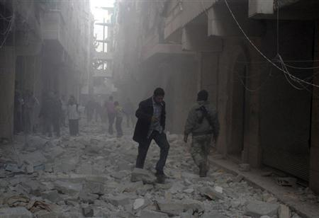 People walk on rubble at a damaged site after what activists said was an air raid by forces loyal to Syrian President Bashar Al-Assad, in Aleppo's al-Saliheen district