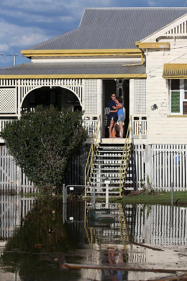 BUNDABERG, AUSTRALIA - JANUARY 29: Residents look on as floods suround thier house as parts of southern Queensland experiences record flooding in the wake of Tropical Cyclone Oswald on January 29, 2013 in Bundaberg, Australia.Four deaths have been confirmed and thousands have been evacuated in Bundaberg as the city faces it's worst flood disaster in history. Rescue and evacuation missions continue today as emergency services prepare to move patients from Bundaberg Hospital to Brisbane amid fears the hospital could lose power. (Photo by Chris Hyde/Getty Images)