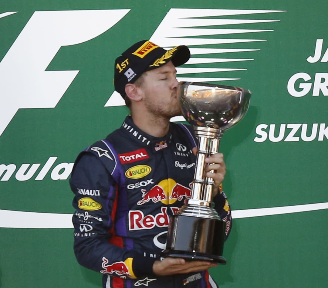 Red Bull Formula One driver Sebastian Vettel of Germany kisses his trophy after winning the Japanese F1 Grand Prix at the Suzuka circuit October 13, 2013. REUTERS/Toru Hanai (JAPAN - Tags: SPORT MOTORSPORT F1)