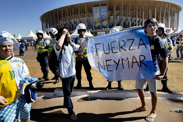 """Fans of Argentina's national soccer team hold a banner with a message that reads in Spanish; """"Strength Neymar,"""" as they wait to enter the Estadio Nacional for the World Cup quarterfinal match between Argentina and Belgium, in Brasilia, Brazil Saturday, July 5, 2014. Neymar, the biggest football star in Brazil, was ruled out of the rest of the tournament after fracturing his third vertebra during Friday's 2-1 quarterfinal win over Colombia. (AP Photo/Rodrigo Abd)"""