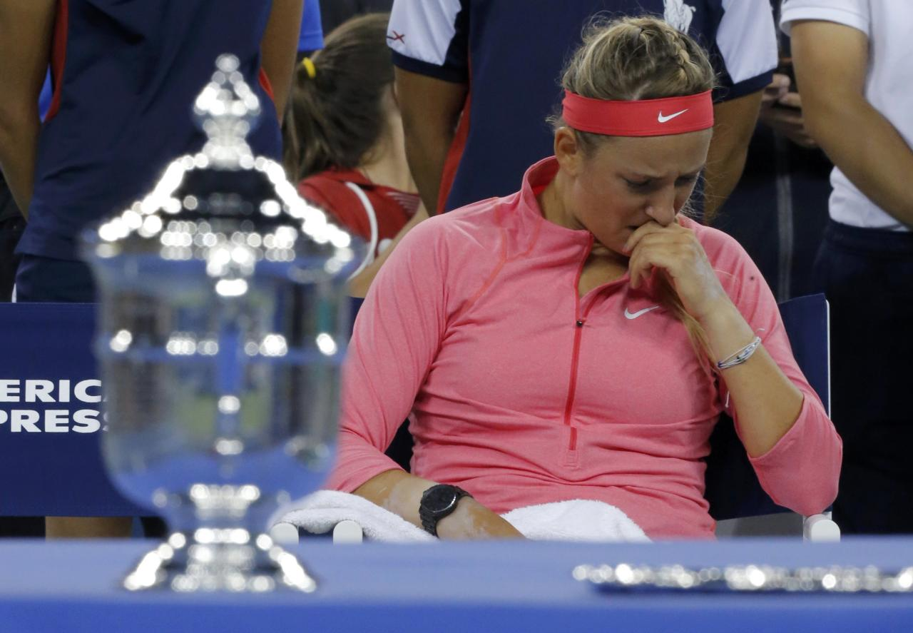 Victoria Azarenka of Belarus wipes her face as she sits by the winner's trophy (L) after being defeated by Serena Williams of the U.S. in their women's singles final match at the U.S. Open tennis championships in New York September 8, 2013. REUTERS/Eduardo Munoz (UNITED STATES - Tags: SPORT TENNIS)