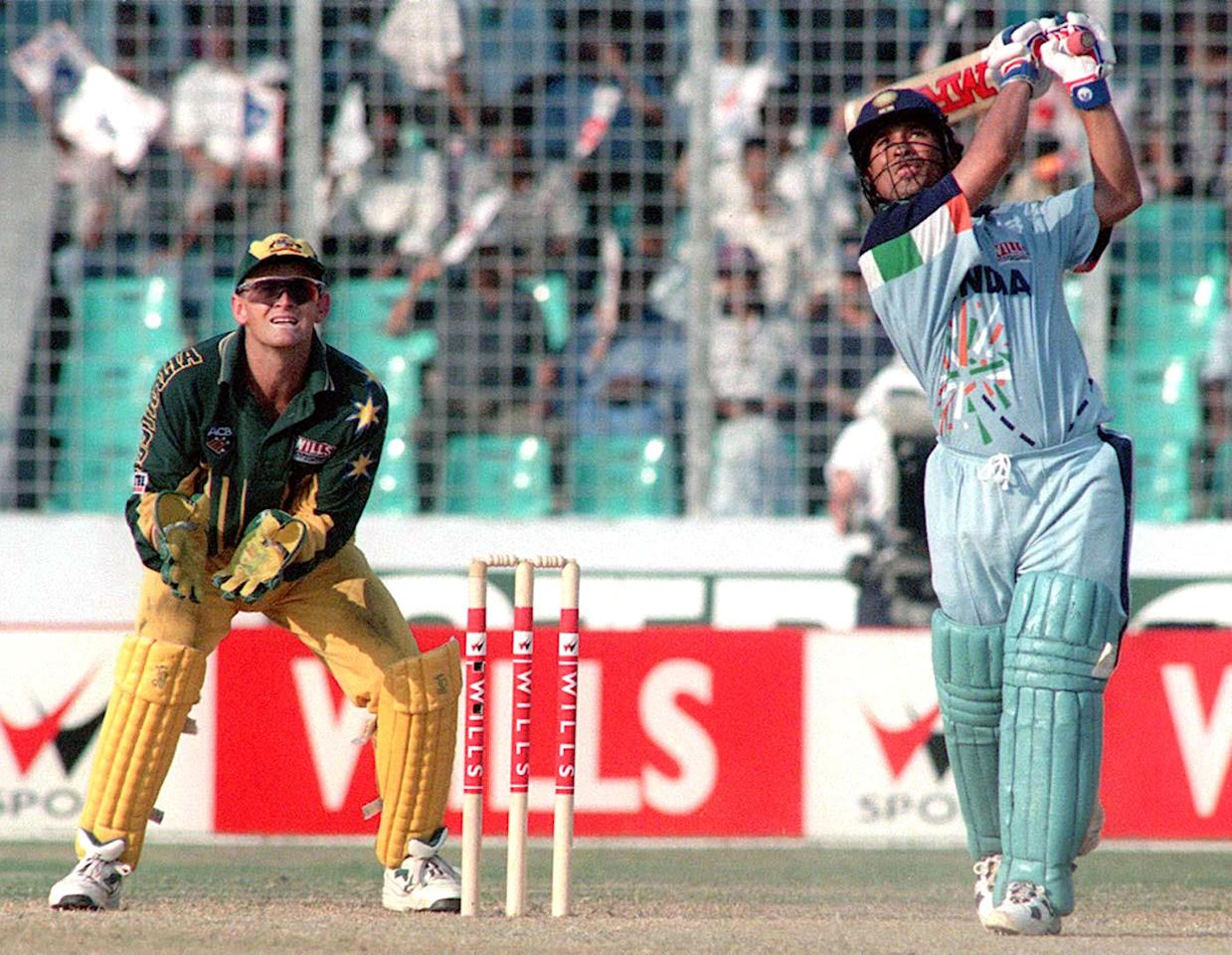 DHAKA, BANGLADESH - OCTOBER 29:  Australian wicket-keeper Adam Gilchrist (L) watches as Indian batsman Sachin Tendulkar lofts a six during his innings of 141 off 127 balls in the mini World Cup quarter-final at Dhaka's National stadium Oct 28. India made 307-8 after being sent to bat. AFP PHOTO AFP PHOTO  (Photo credit should read MUFTY MUNIR/AFP/Getty Images)