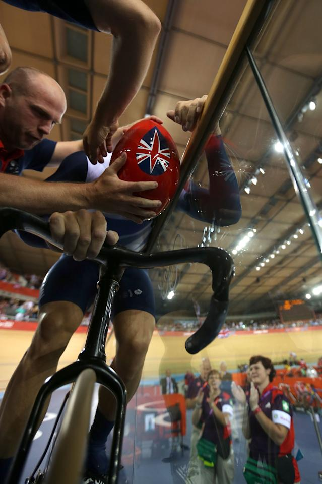 LONDON, ENGLAND - AUGUST 02:  Sir Chris Hoy of Great Britain is aided with removing his helmet after setting a new world record in the Men's Team Sprint Track Cycling final on Day 6 of the London 2012 Olympic Games at Velodrome on August 2, 2012 in London, England.  (Photo by Bryn Lennon/Getty Images)