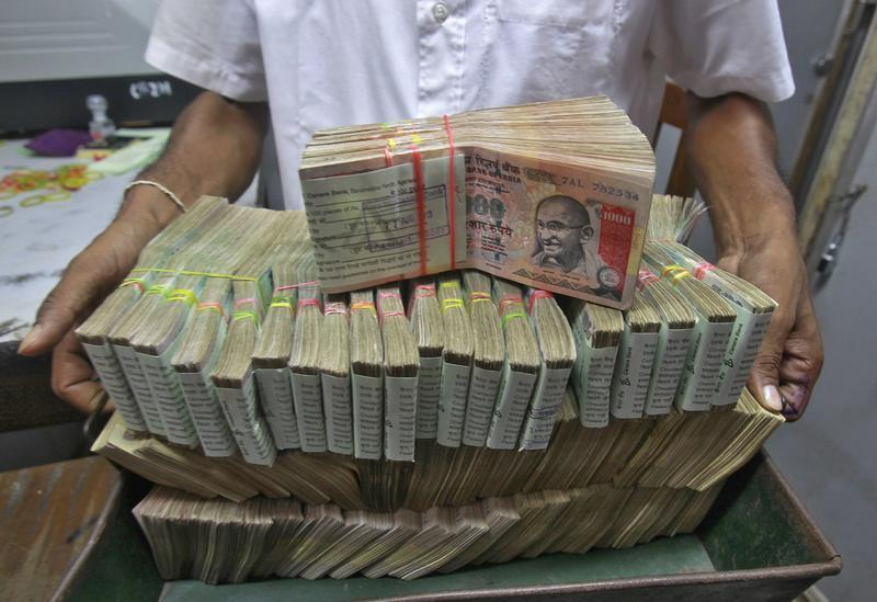 An employee poses with the bundles of Indian rupee notes inside a bank in Agartala
