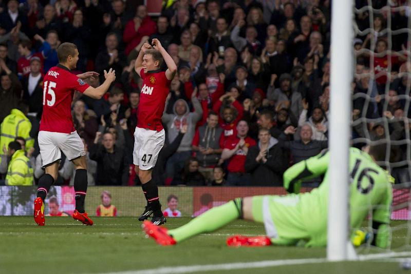 Manchester United's James Wilson, centre left, celebrates with teammate Nemanja Vidic after scoring past Hull City's goalkeeper Eldin Jakupovic during their English Premier League soccer match at Old Trafford Stadium, Manchester, England, Tuesday May 6, 2014