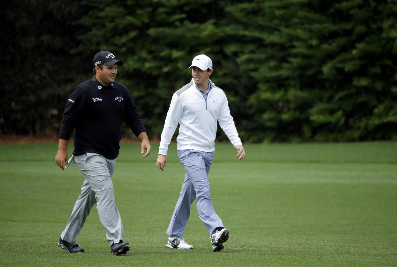 U.S. golfer Patrick Reed (L) and Rory McIlroy of Northern Ireland walk up the 13th fairway during a practice round ahead of the Masters golf tournament at the Augusta National Golf Club in Augusta, Georgia April 8, 2014. REUTERS/Mike Blake (UNITED STATES - Tags: SPORT GOLF)