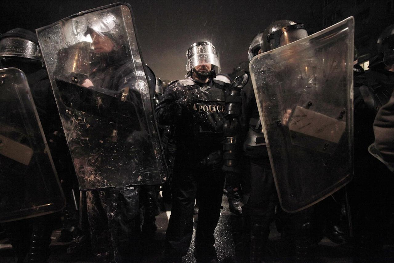 Riot police form up after clashes with demonstrators after a protest against high electricity prices in Sofia, on late Tuesday, Feb. 19, 2013. Bulgaria's prime minister announced on Tuesday that the license held by a Czech company for power distribution in parts of the Balkan country will be revoked following protests against high electricity prices. (AP Photo/Valentina Petrova)
