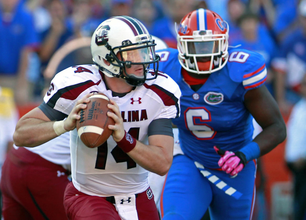South Carolina quarterback Connor Shaw scrambles out of the pocket as his pressured by Florida defensive back Dante Fowler Jr. (6) during the first half of an NCAA college football game, Saturday, Oct. 20, 2012, in Gainesville, Fla. (AP Photo/John Raoux)