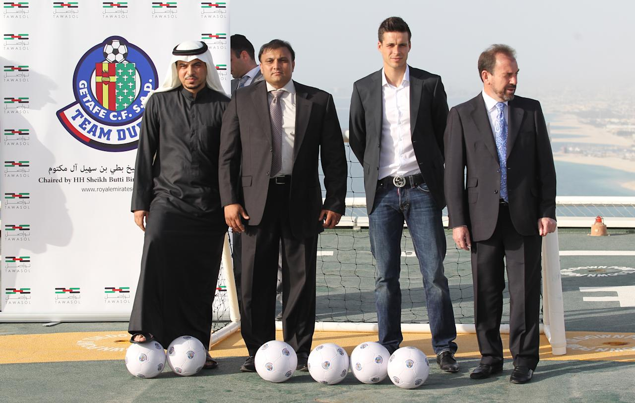 """Suleiman al-Butti, (2R), project manager of Royal Emirates Group, Angel Torres, (R), president of Spanish La Liga football club Getafe, Kaiser Rafiq, the group's managing director (2L) and Spanish striker Manu del Moral (2R) pose after Royal Emirates Group, which is chaired by a member of Dubai's ruling Al-Maktoum family, announced it has signed a deal to buy struggling football club Getafe, on April 21, 2011 in Dubai. Rafiq told a news conference in Dubai it has agreed to buy 100 percent of the club for """"between 70 and 90 million euros"""" (101 and 130 million dollars), with the exact amount confidential. AFP PHOTO/KARIM SAHIB"""