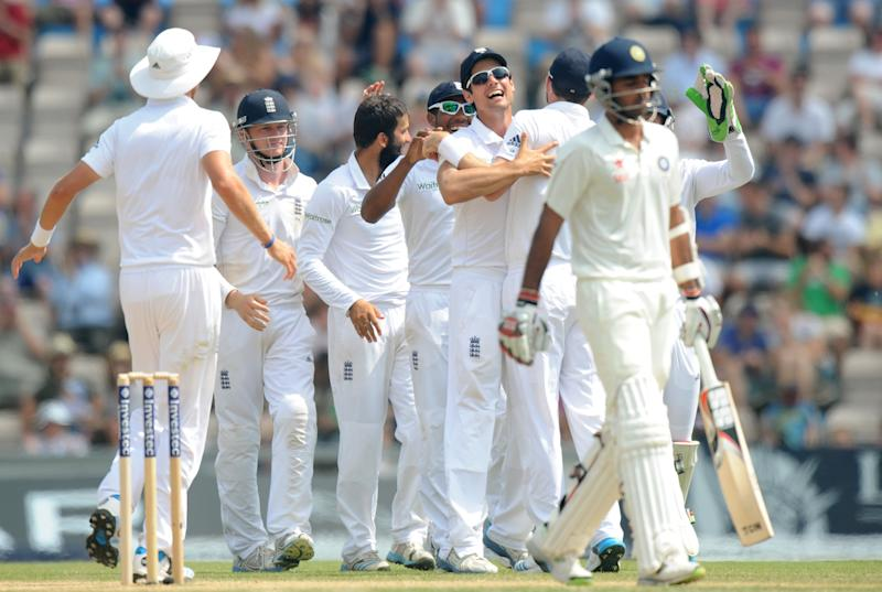 England's Moeen Ali (left) celebrates with Alistair Cook (centre) who can't hide his joy after taking the wicket of India's Bhuvneshwar Kumar on the fifth day of the third Test match at The Aegeas Bowl in Southampton, on July 31, 2014