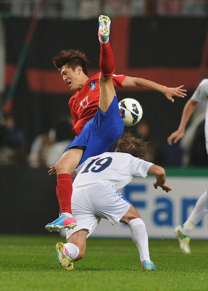 SEOUL, SOUTH KOREA - JUNE 11:  Lee Chungyong of South Korea is tackled by Vitaliy Denisov of Uzbekistan during the FIFA World Cup qualifier match between South Korea and Uzbekistan at Seoul World Cup Stadium on June 11, 2013 in Seoul, South Korea.  (Photo by Atsushi Tomura/Getty Images)