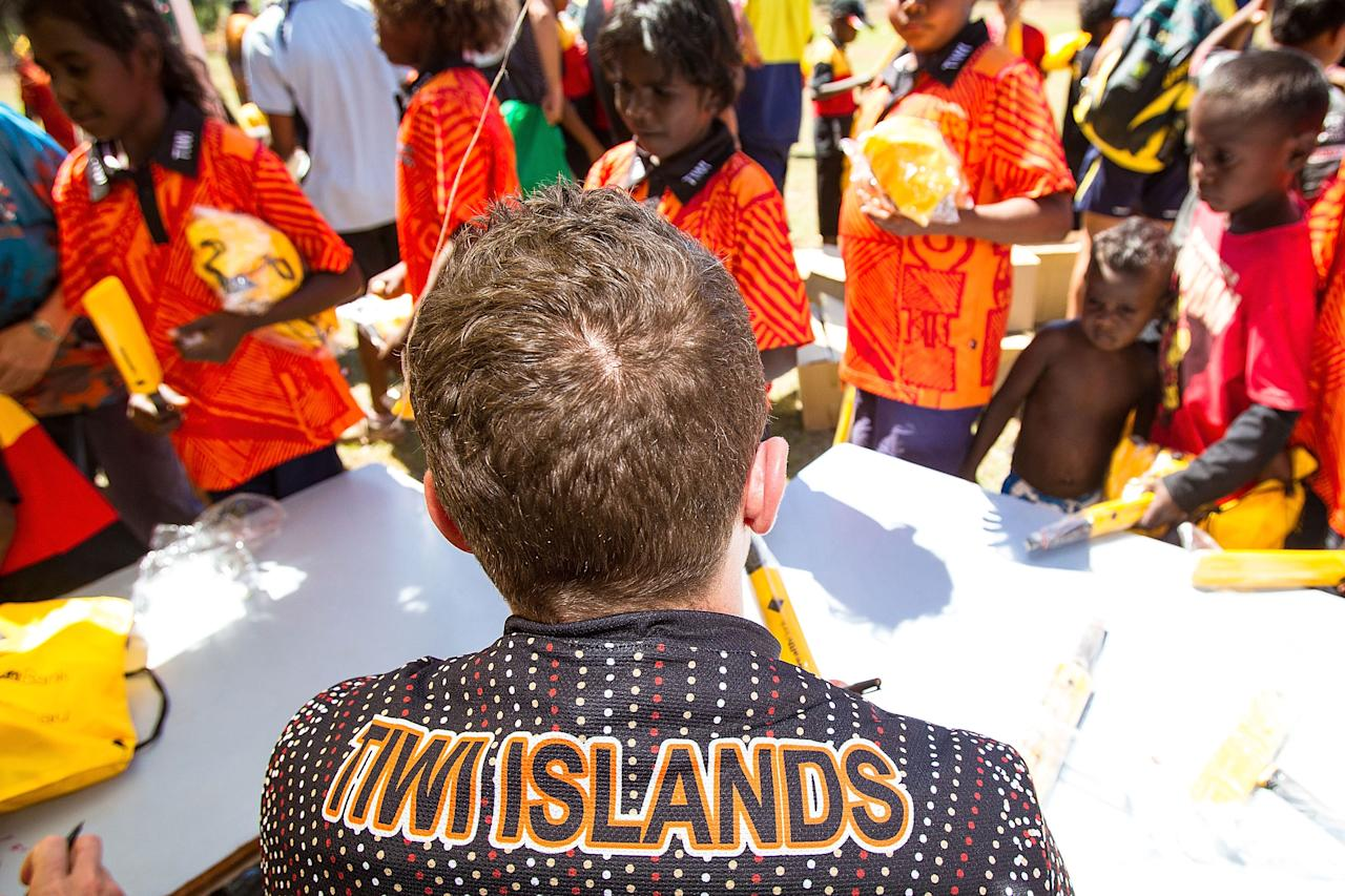 DARWIN, AUSTRALIA - AUGUST 10:  Peter Siddle of the Australian cricket team signs autographs during a visit to Pirlangimpi of the Tiwi Islands on August 10, 2012 on the Tiwi Islands, Australia.  (Photo by Mark Nolan/Getty Images)