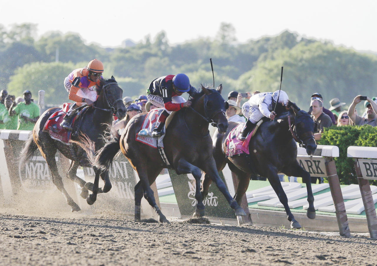 Tonalist, center, with Joel Rosario, up beats Commissioner, right, with Javier Castellano up, to win the Belmont Stakes horse race, Saturday, June 7, 2014, in Elmont, N.Y. Medal Count, at left, with Robby Albarado up, finished third. (AP Photo/Seth Wenig)