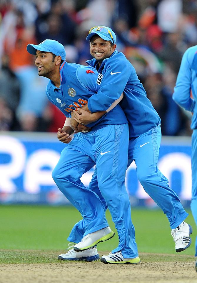 India's Rohit Sharma (L) celebrates with India's Suresh Raina after running out England's Tim Bresnan during the 2013 ICC Champions Trophy Final cricket match between England and India at Edgbaston in Birmingham, central England on 23, June 2013.  India scored 129 runs for the loss of seven wickets after the rain delayed match was reduced reduced to the bare minimum of 20 overs per side required to produced a result.   AFP PHOTO/ANDREW