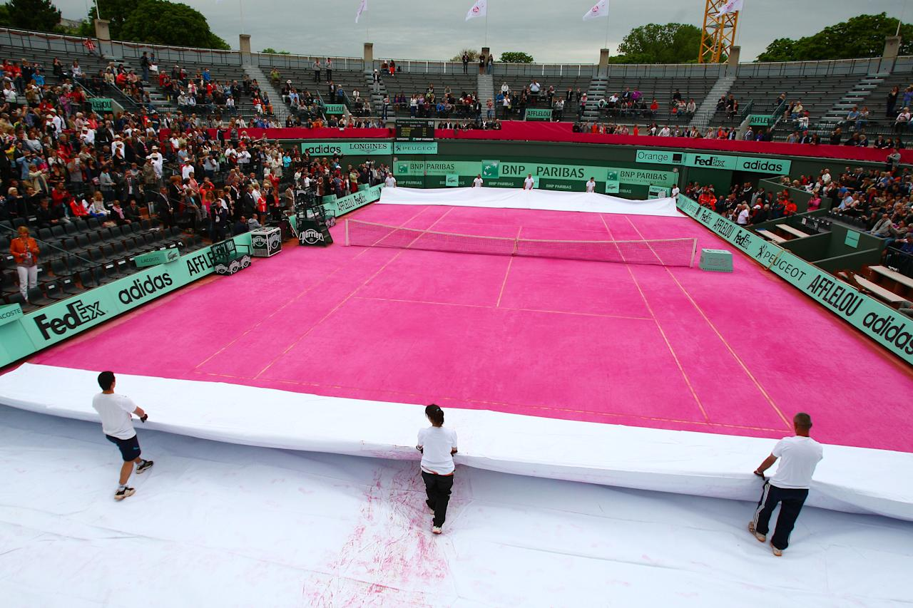 PARIS, FRANCE - JUNE 07: Groundstaff unveil a pink clay court prior to the women's legends doubles semi final match between Martina Navratilova of USA and Jana Novotna of Czech Republic and Nathalie Tauziat and Sandrine Testud of France during day 12 of the French Open at Roland Garros on June 7, 2012 in Paris, France.  (Photo by Getty Images/Getty Images)