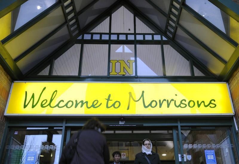 Shoppers walk through the entrance of a Morrisons supermarket in west London