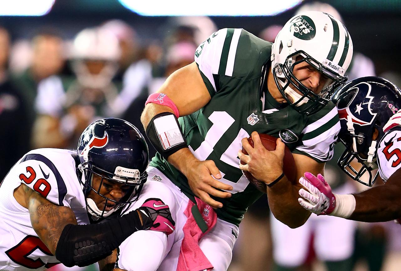 EAST RUTHERFORD, NJ - OCTOBER 08:  Tim Tebow #15 of the New York Jets is tackled by Glover Quin #29 and Bradie James #53 of the Houston Texans in the first half at MetLife Stadium on October 8, 2012 in East Rutherford, New Jersey.  (Photo by Al Bello/Getty Images)