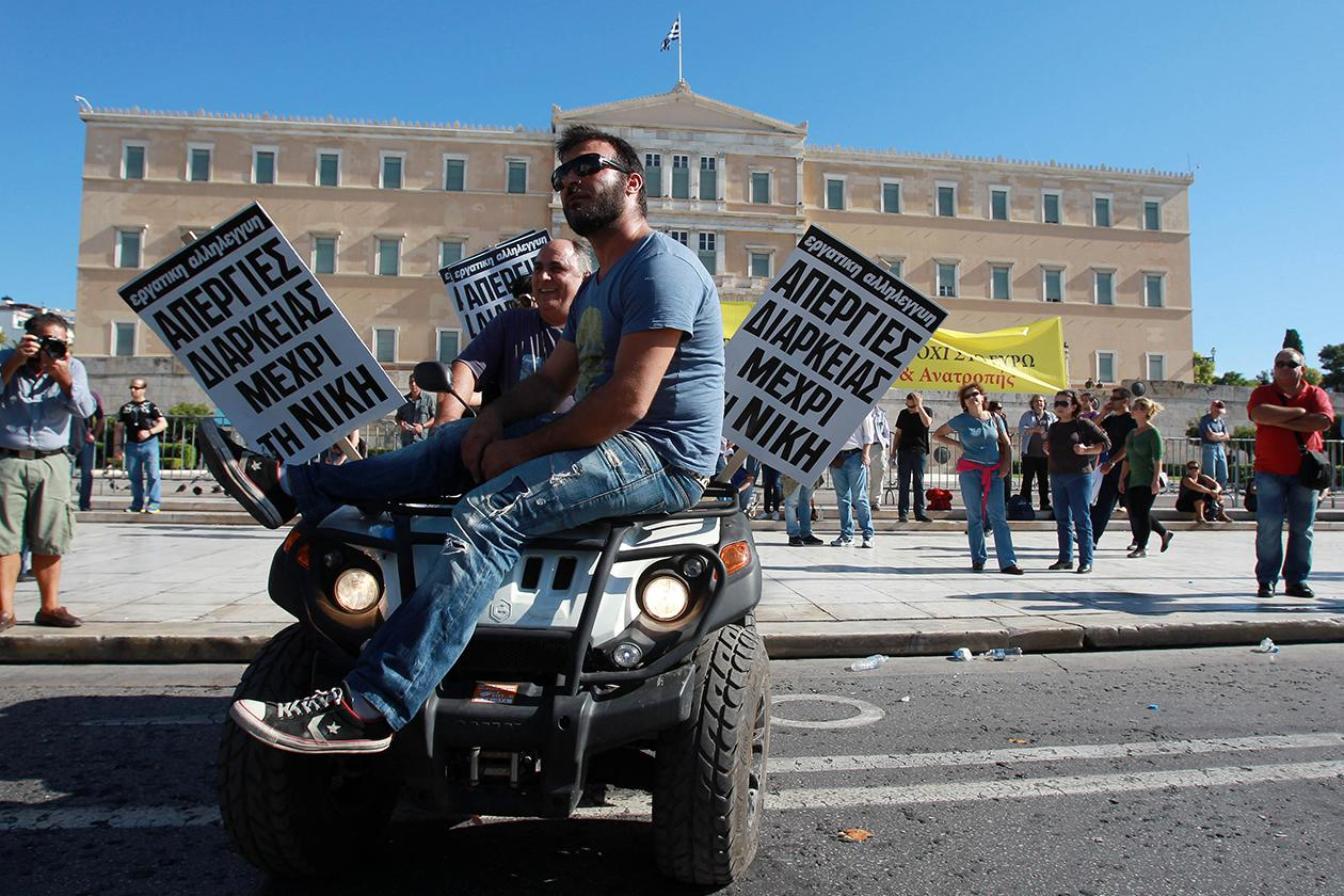 Protesters on a quad bike hold signs reading ''Endless strikes until we win'' in front of the Greek parliament.