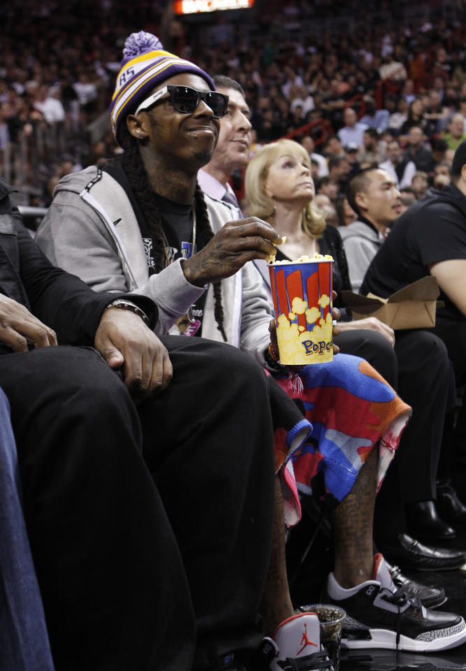 Rapper Lil Wayne eats popcorn while watching an NBA basketball game between the Miami Heat and the Los Angeles Lakers, Thursday, Jan. 19, 2012, in Miami. (AP Photo/Lynne Sladky)