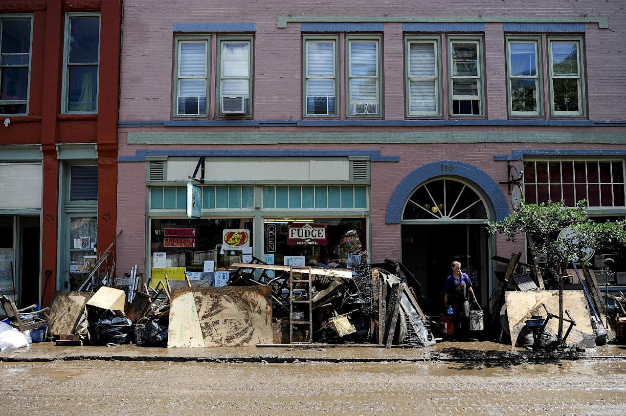 Business owners pile muddy furniture outside their building off Canon Avenue Saturday, Aug. 10, 2013 in Manitou Springs, Colo. Friday's torrential rains swept mud, boulders and other debris from the burn scar down U.S. 24, washing away vehicles and damaging several homes and businesses in the area. (AP Photo/The Colorado Springs Gazette, Michael Ciaglo) MAGS OUT