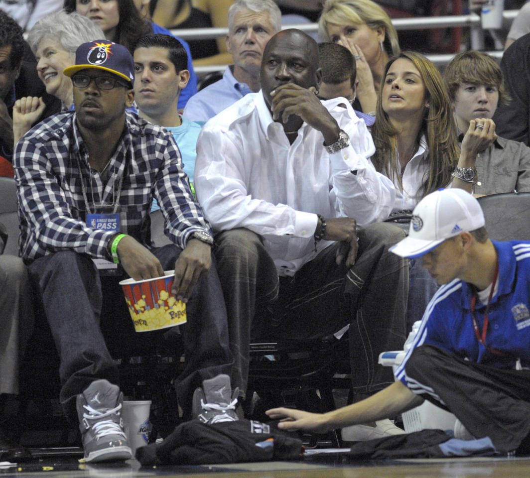 FILE - In this April 21, 2010, file photo, Central Florida's Marcus Jordan, left, sits next to his father, Charlotte Bobcats majority owner Michael Jordan, center. and Yvette Prieto, right, watching the second half of Game 2 of a first round NBA basketball playoff game between the Orlando Magic and the Charlotte Bobcats in Orlando, Fla.