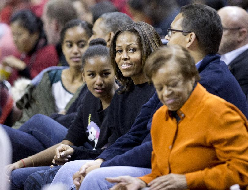 President Barack Obama, with first lady Michelle Obama, second from right, and their daughters Malia, left, and Sasha, second from left, and  mother-in-law Marian Robinson, right, watch a basketball game between his  brother-in-law Oregon State Beavers Coach Craig Robinson's team play against the Maryland Terrapins, Sunday, Nov. 17, 2013, at the Comcast Center in College Park, Md. (AP Photo/Manuel Balce Ceneta)