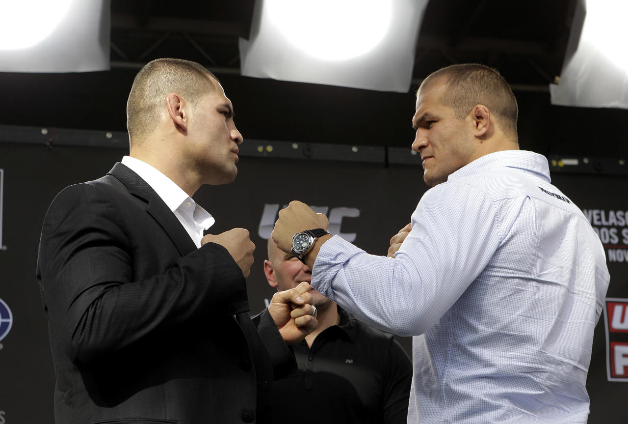 Mixed martial arts fighters Cain Velasquez, left, and Junior Dos Santos pose for photos after a news conference in Los Angeles, Wednesday, Nov. 9, 2011. Velasquez will attempt to defend his UFC heavyweight title against Junior Dos Santos on Saturday, Nov. 12, in Anaheim, Calif. (AP Photo/Jae C. Hong)