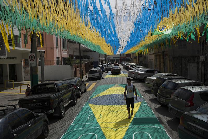 A man walks along a street decorated for the upcoming World Cup in Rio de Janeiro, Brazil, Wednesday, May 14, 2014. The international soccer tournament will be the first in the South American nation since 1950
