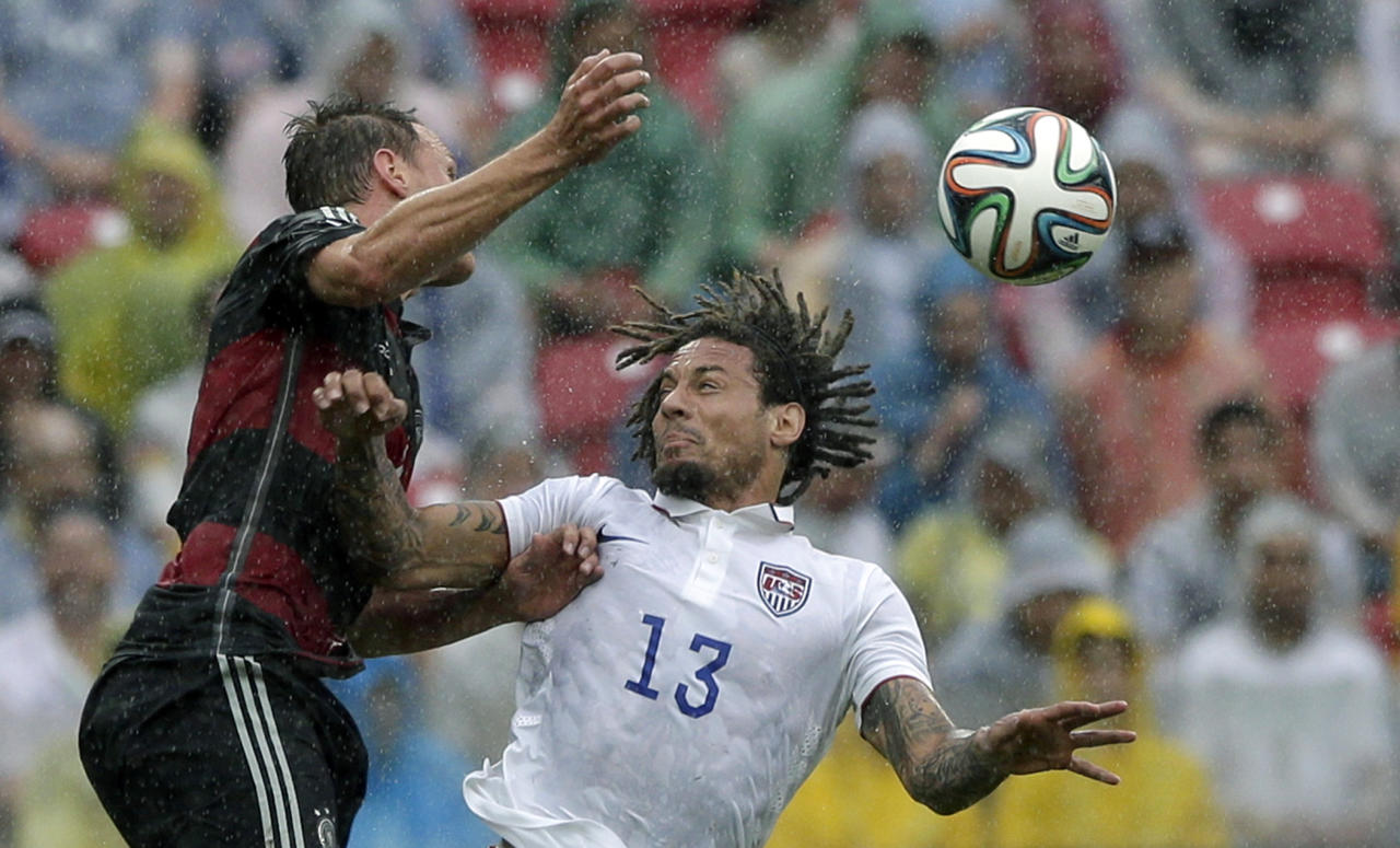 Germany's Benedikt Hoewedes, left, and United States' Jermaine Jones go for a header during the group G World Cup soccer match between the USA and Germany at the Arena Pernambuco in Recife, Brazil, Thursday, June 26, 2014. (AP Photo/Matthias Schrader)