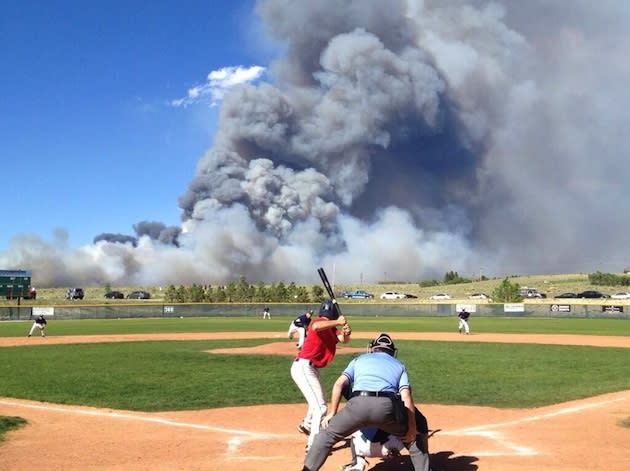 The Black Forest fire is seen in the back of the Pine Creek baseball diamond — Twitter