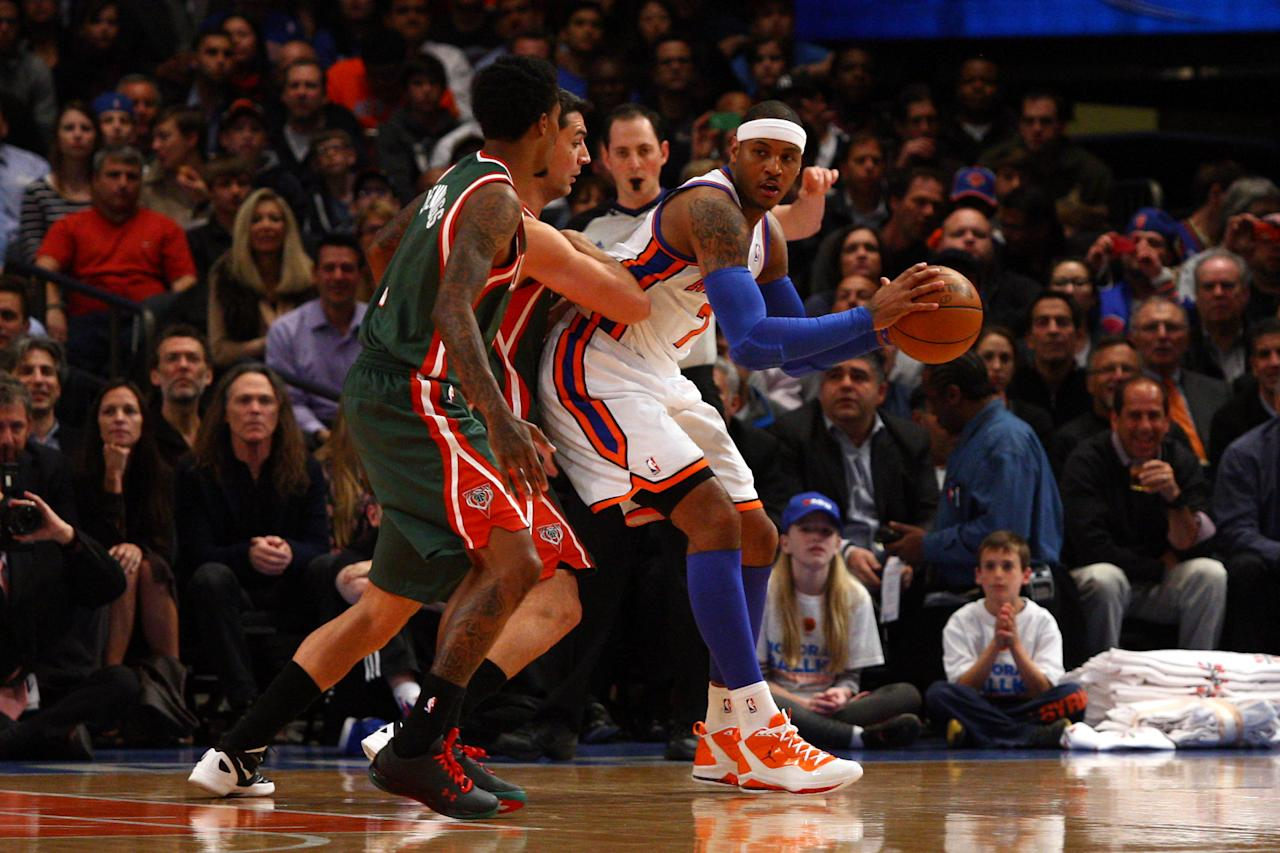 NEW YORK, NY - MARCH 26:  Carmelo Anthony #7 of the New York Knicks looks to pass in the post in the first half against Carlos Delfino #10 and Brandon Jennings #3 of the Milwaukee Bucks at Madison Square Garden on March 26, 2012 in New York City. NOTE TO USER: User expressly acknowledges and agrees that, by downloading and or using this photograph, User is consenting to the terms and conditions of the Getty Images License Agreement.  (Photo by Chris Chambers/Getty Images)