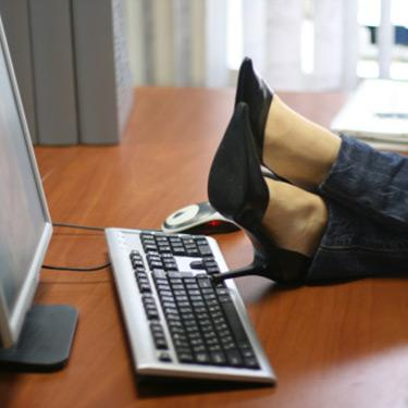 Woman-with-legs-propped-up-on-computer-desk_web