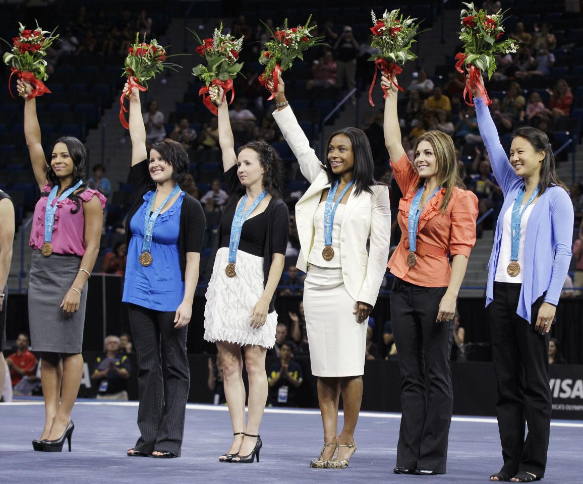 United States gymnasts from the 2000 Sydney Olympics hold up their bronze medals following a ceremony in Hartford, Conn., Wednesday, Aug. 11, 2010.  The U.S. women's team received the third-place medals that were stripped from China because a member of that team was found to be underage.  From left ro right, are: Tasha Schwikert, Elise Ray, Kristin Maloney, Dominique Dawes, Jamie Dantzscher and Amy Chow.  (AP Photo/Charles Krupa)