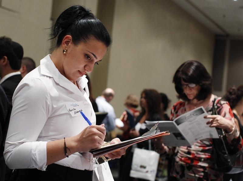 A woman fills out an application from a jewelry and gem company during the GIA Jewelry Career Fair in New York
