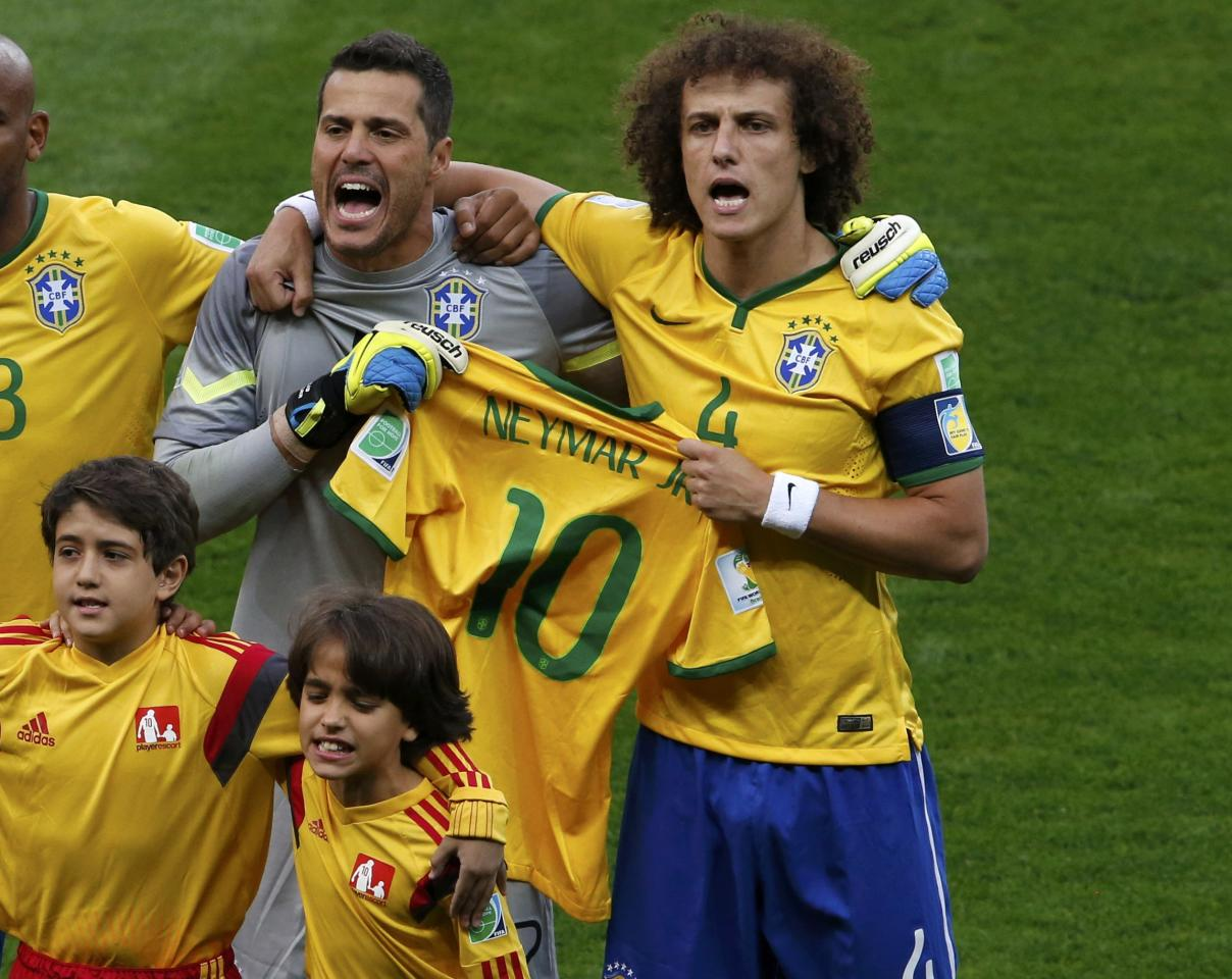 Brazil's David Luiz (R) and goalkeeper Julio Cesar hold jersey of their teammate Neymar as they sing the national anthem before their 2014 World Cup semi-finals against Germany at the Mineirao stadium in Belo Horizonte July 8, 2014. REUTERS/David Gray (BRAZIL - Tags: SOCCER SPORT WORLD CUP)