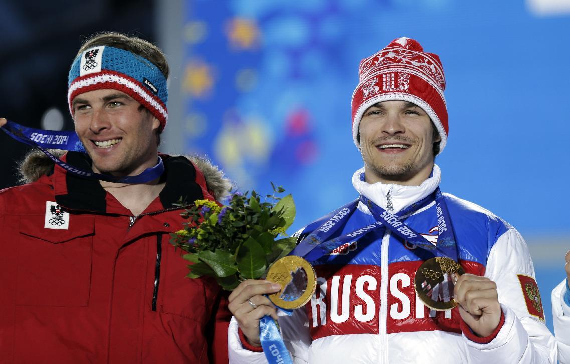 Austria's Benjamin Karl, the bronze medalist in the men's snowboard parallel slalom, left, smiles while standing next to gold medalist Vic Wild of Russia, who also won the gold medal in the men's snowboard parallel giant slalom, during their medals ceremony at the 2014 Winter Olympics, Saturday, Feb. 22, 2014, in Sochi, Russia. (AP Photo/David Goldman)