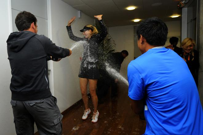 PARIS, FRANCE - JUNE 09:  Maria Sharapova of Russia is sprayed with champagne by her physical trainer Juan Reque (L) and her hitting partner Cecil Mamiit (R) as she makes her way to her changing room after her women's singles final against Sara Errani of Italy during day 14 of the French Open at Roland Garros on June 9, 2012 in Paris, France.  (Photo by Sindy Thomas - Pool/Getty Images)