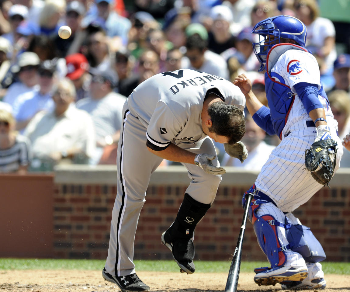 CHICAGO, IL - MAY 18:  Paul Konerko #14 of the Chicago White Sox is hit in the face by a pitch in the third inning as Welington Castillo #54 of the Chicago Cubs looks on May 18 2012 at Wrigley Field in Chicago, Illinois. Konerko had to leave the game.  (Photo by David Banks/Getty Images)
