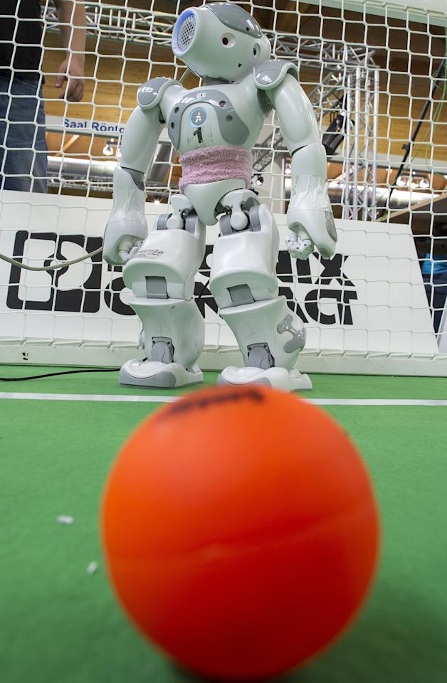 MAGDEBURG, GERMANY - APRIL 26:  A robot on the play field at the 2013 RoboCup German Open tournament on April 26, 2013 in Magdeburg, Germany. The robots, which are a model called Nao, manufactured by Aldebaran Robotics, perform autonomously and communicate with one another via WLAN. The three-day tournament is hosting 43 international teams and 158 German junior teams that compete in a variety of disciplines, including soccer, rescue and dance.  (Photo by Jens Schlueter/Getty Images)